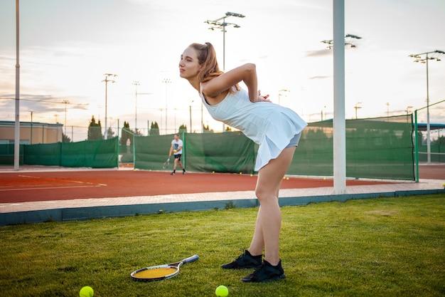 Bella giovane donna in abiti sportivi bianchi si è fatta male giocando a tennis al campo da tennis