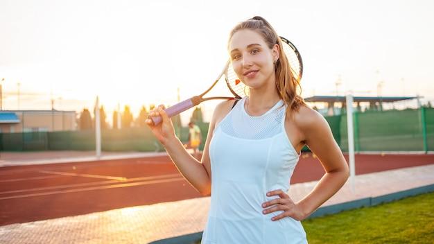 Bella giovane donna in abiti sportivi bianchi in posa con racchetta da tennis alla corte