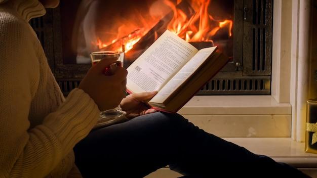 Bella giovane donna in maglione bianco che beve tè e legge un libro al caminetto