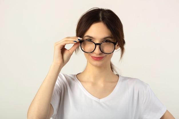 Bella giovane donna in una maglietta bianca su sfondo bianco con gli occhiali