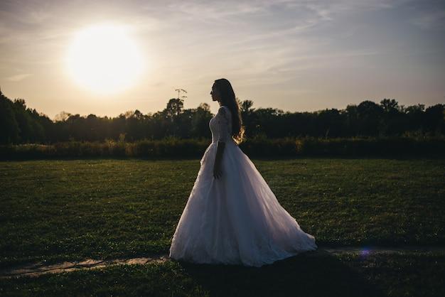 Bella giovane donna in un abito da sposa bianco e stivali neri al tramonto.