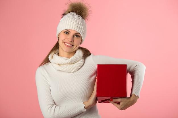 Bella giovane donna in cappello invernale con un regalo in mano su uno sfondo rosa