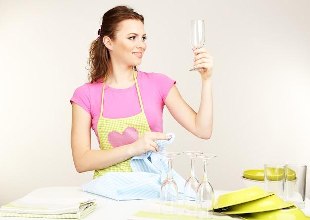 La bella giovane donna asciuga gli utensili puliti in cucina su gray