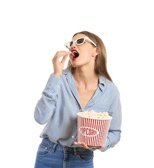 Bella giovane donna con i vetri del cinema 3d che mangia popcorn sulla superficie bianca