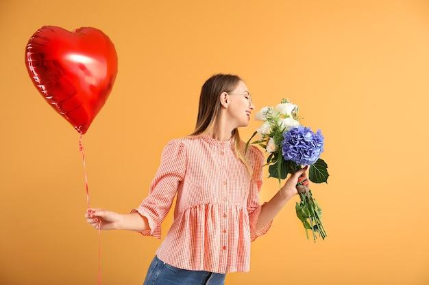 Bella giovane donna con mongolfiera e fiori su sfondo colorato