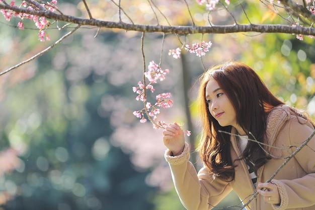 Bella giovane donna con fiori di ciliegio in fiore