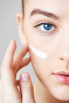 La bella giovane donna con gli occhi azzurri senza trucco applica la crema sulla sua guancia