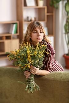 Bella giovane donna con un mazzo di fiori di mimosa a casa