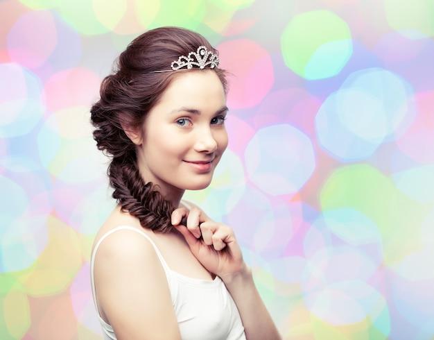 Bella giovane donna con una treccia che indossa un diadema di diamanti