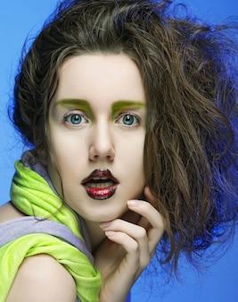 Bella giovane donna con trucco luminoso su sfondo blu