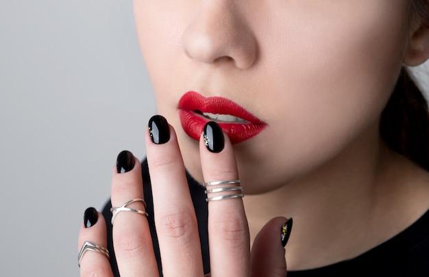 Bellissima giovane donna con il trucco luminoso e il design delle unghie nere