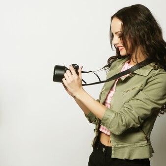 Bella giovane donna con fotocamera su sfondo grigio