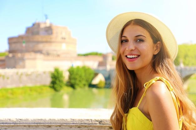 Bella giovane donna con castel sant angelo, roma, italia