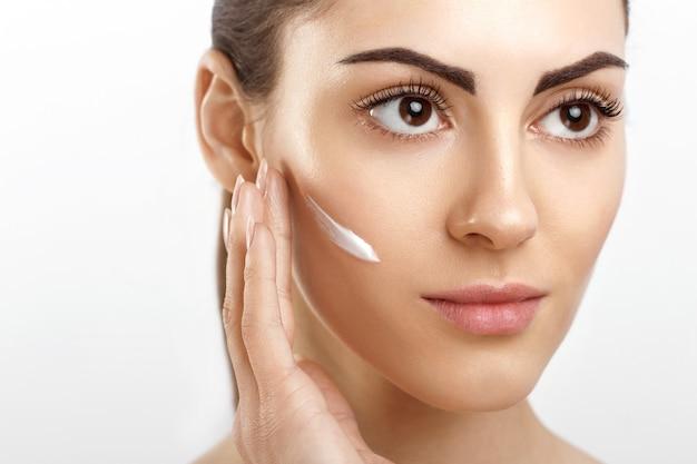 Bella giovane donna con pelle fresca pulita che applica crema