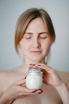 Una bella giovane donna con la pelle fresca e pulita tiene un barattolo bianco con una crema per il viso