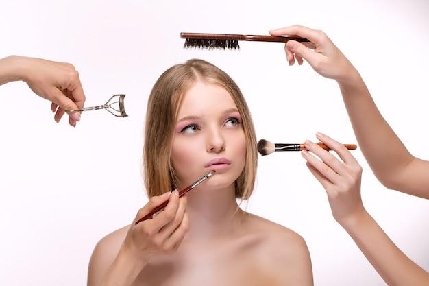 Bella giovane donna con la pelle fresca e pulita, proponendo un prodotto con i gesti del pennello trucco