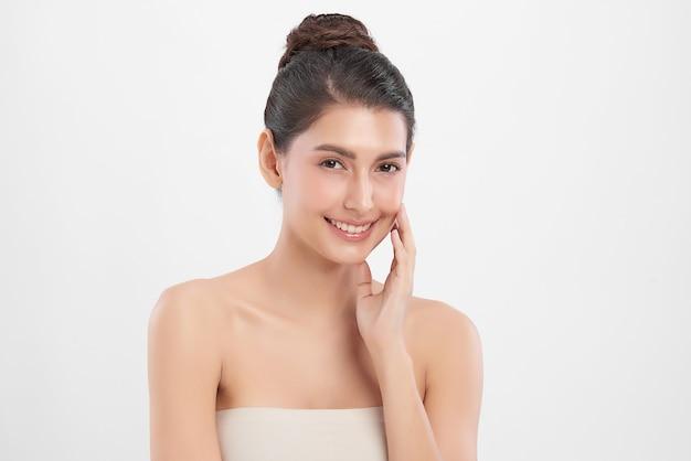 Bella giovane donna con pelle fresca pulita sulla parete bianca