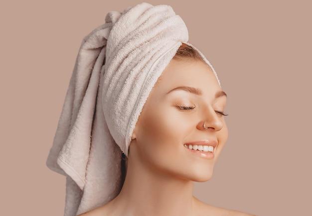Bella giovane donna con pelle pulita e asciugamano in testa su una parete beige