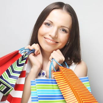 Bella giovane donna con borse della spesa colorate su sfondo grigio