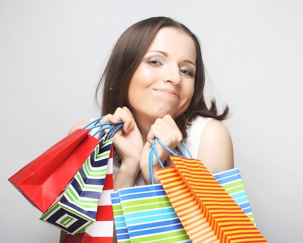 Bella giovane donna con borse della spesa colorate su grigio