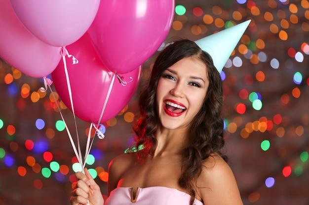 Bella giovane donna con palloncini colorati contro luci sfocate