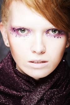 Bella giovane donna con il trucco di moda creativa