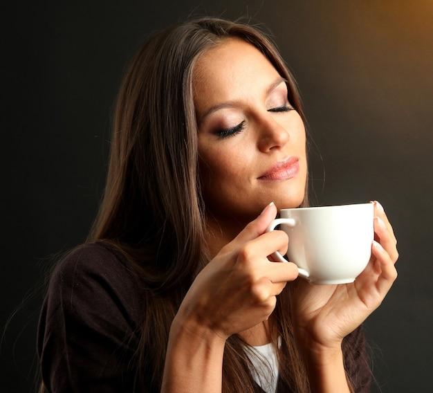 Bella giovane donna con una tazza di caffè, su sfondo marrone