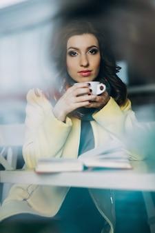 Bella giovane donna con una tazza di tè o caffè al bar