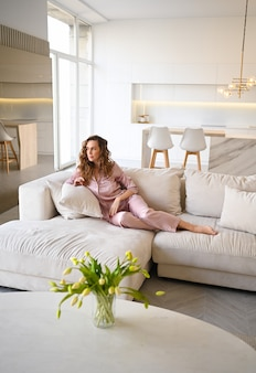 Bella giovane donna con i capelli ricci in pigiama rosa sdraiato sul divano divano bianco al mattino. soggiorno in stile scandinavo e interni cucina.