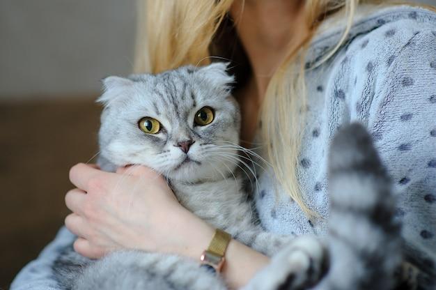 Bella giovane donna con simpatico gatto su un letto