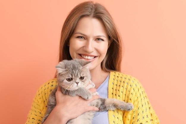 Bella giovane donna con simpatico gatto su sfondo colorato