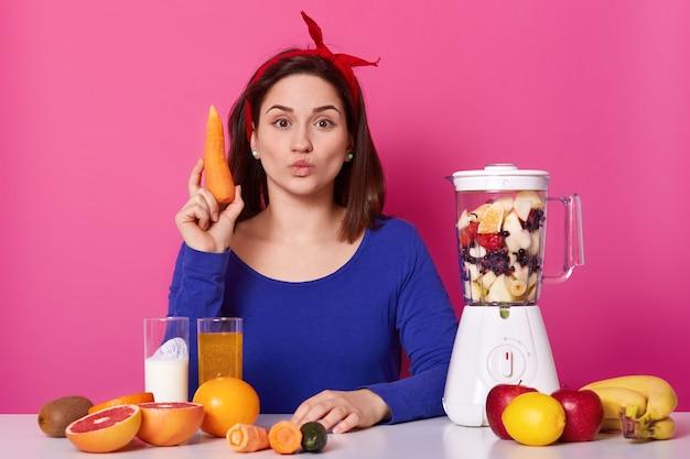 Bellissima giovane donna con i capelli scuri, mantiene le labbra arrotondate, tiene in mano la carota, produce frullati freschi, ha il frullatore pieno di frutta sul tavolo. alla femmina piace mangiare sano. concetto di stile di vita.