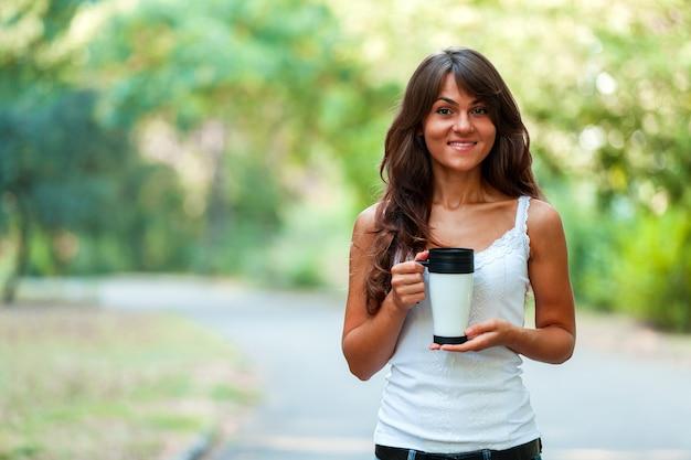 Bella giovane donna con una tazza di caffè usa e getta, bevendo caffè nelle sue mani
