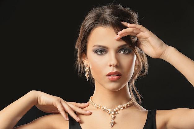 Bella giovane donna con gioielli eleganti su sfondo scuro