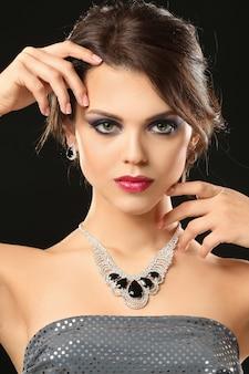 Bella giovane donna con gioielli eleganti