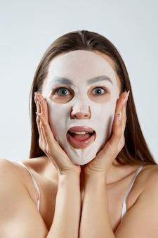 Bella giovane donna con maschera facciale. procedura cosmetica. girl beauty spa e cosmetologia.