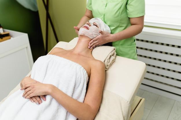 Bella giovane donna con la maschera facciale che ottiene il trattamento di massaggio della stazione termale al salone della stazione termale di bellezza. trattamento di bellezza per il viso.