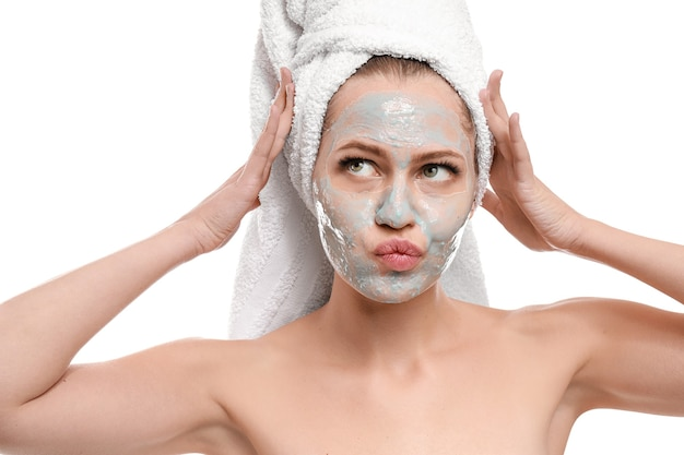 Bella giovane donna con maschera facciale su sfondo bianco