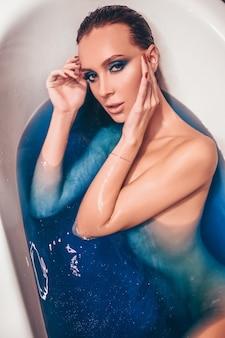 Bella giovane donna con trucco di moda, in posa il bagno in una vasca retrò piena di acqua bomba cosmica colorata blu. spa e concetto di salone di bellezza, corpo e cura della pelle.