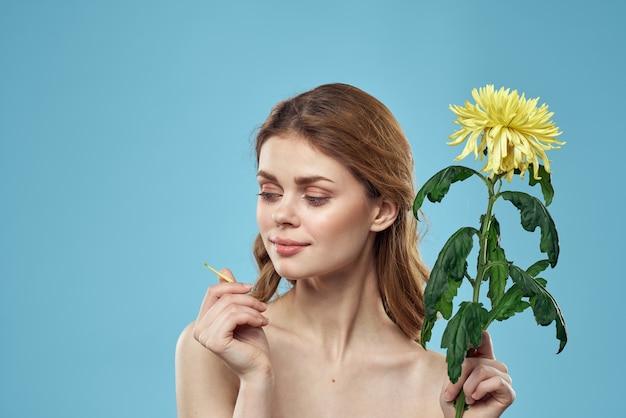 Bella giovane donna con fiore in posa in studio su sfondo blu, romantica immagine tenera