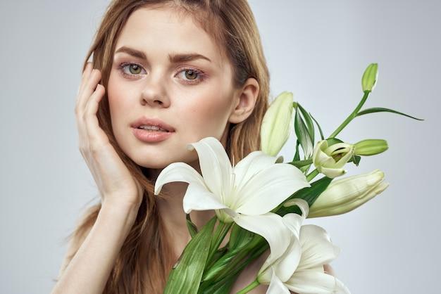 Bella giovane donna con fiore in posa in studio su sfondo chiaro, romantica immagine tenera, ritratto di donna