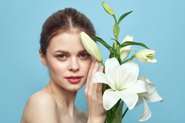 Bella giovane donna con fiore in posa in studio