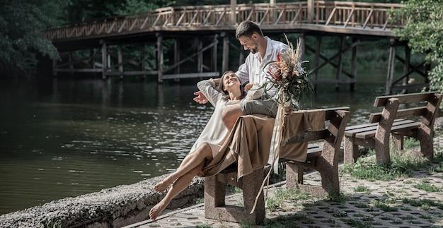 Una bellissima giovane donna con fiori e suo marito sono seduti su una panchina