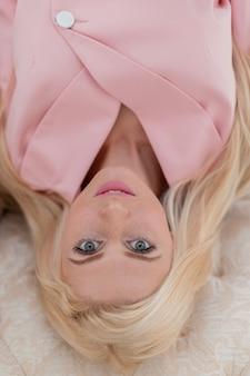 Bella giovane donna con le lentiggini in un vestito alla moda rosa si trova su una vista dall'alto di un divano