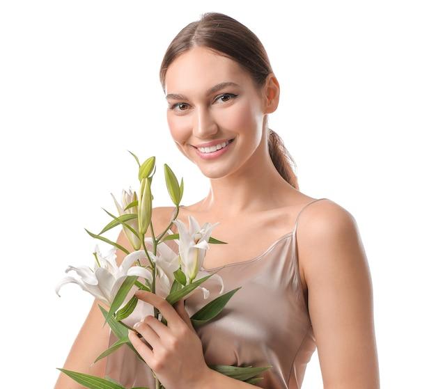 Bella giovane donna con gigli freschi su sfondo bianco