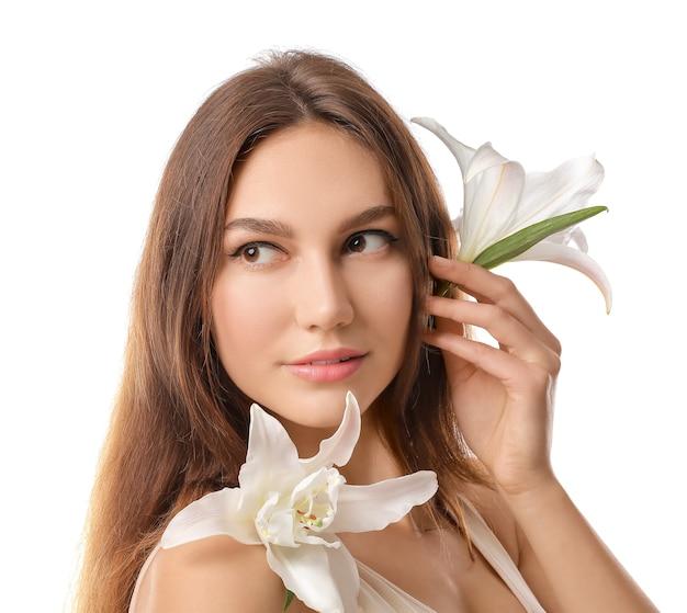 Bella giovane donna con gigli freschi su bianco