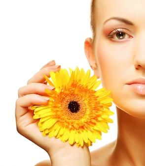 Bella giovane donna con fiore gerber isolato su sfondo bianco