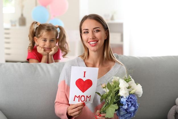 Bella giovane donna con i regali di sua figlia a casa