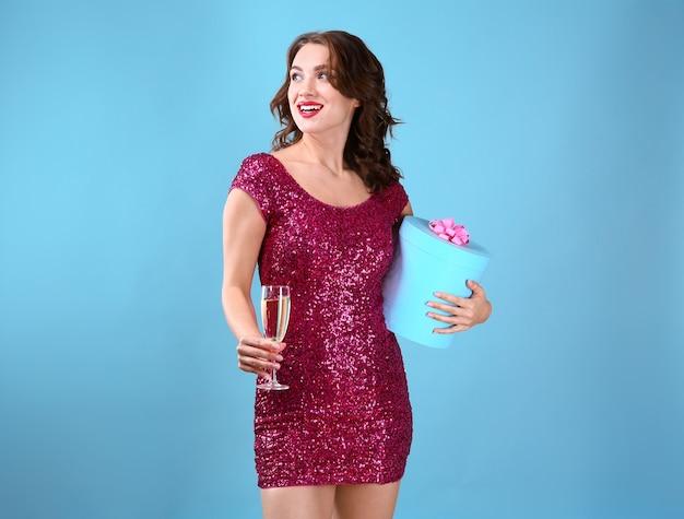 Bella giovane donna con un bicchiere di champagne e regalo