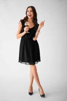 Bella giovane donna con un bicchiere di vino sulla superficie chiara